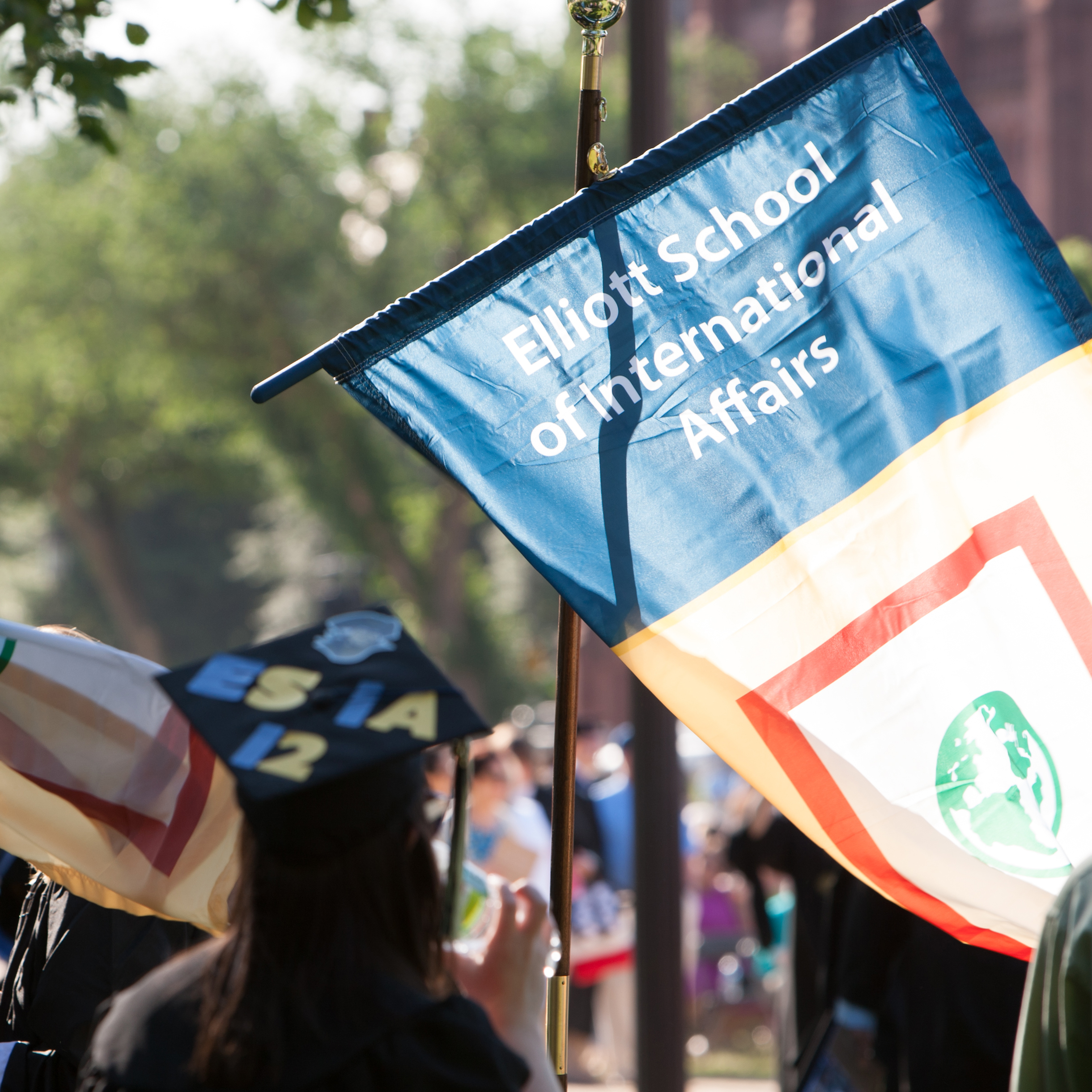 Graduate cap in crowd with a flag that reads Elliott School of International Affairs