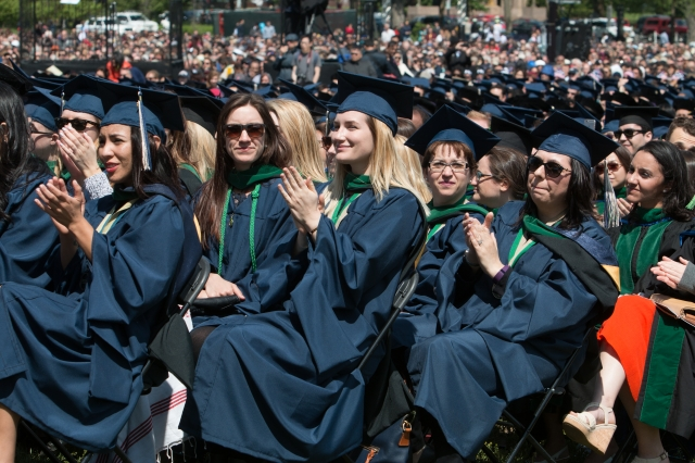 Photo of graduates in full academic dress clapping