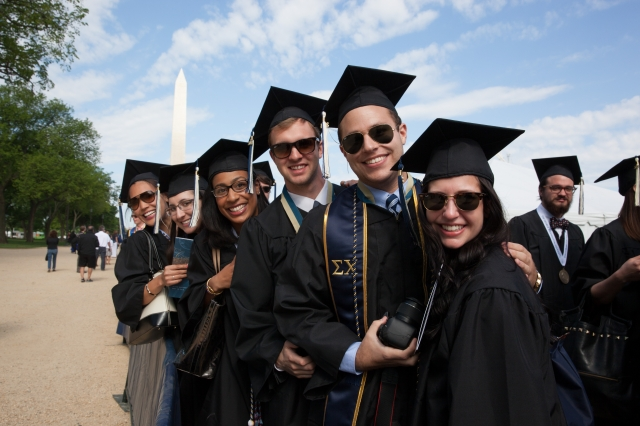Graduates smiling together in front of Washington Monument.