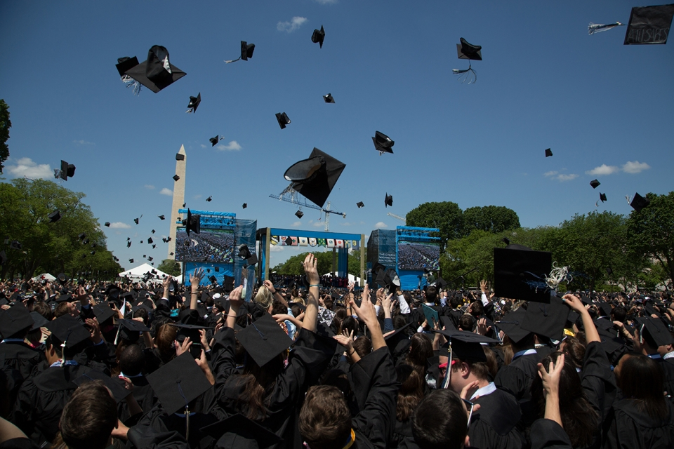 Students throwing commencement caps in the air