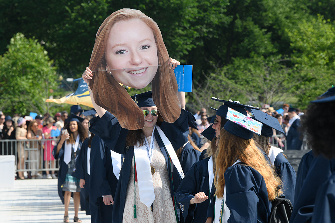 A graduate holding a very large carboard cutout of her friends head