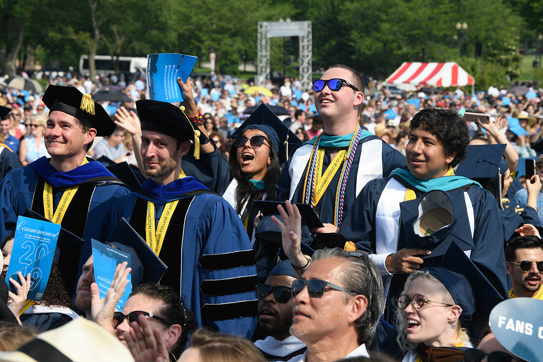 A group of 2019 doctoral graduates standing in a crowd