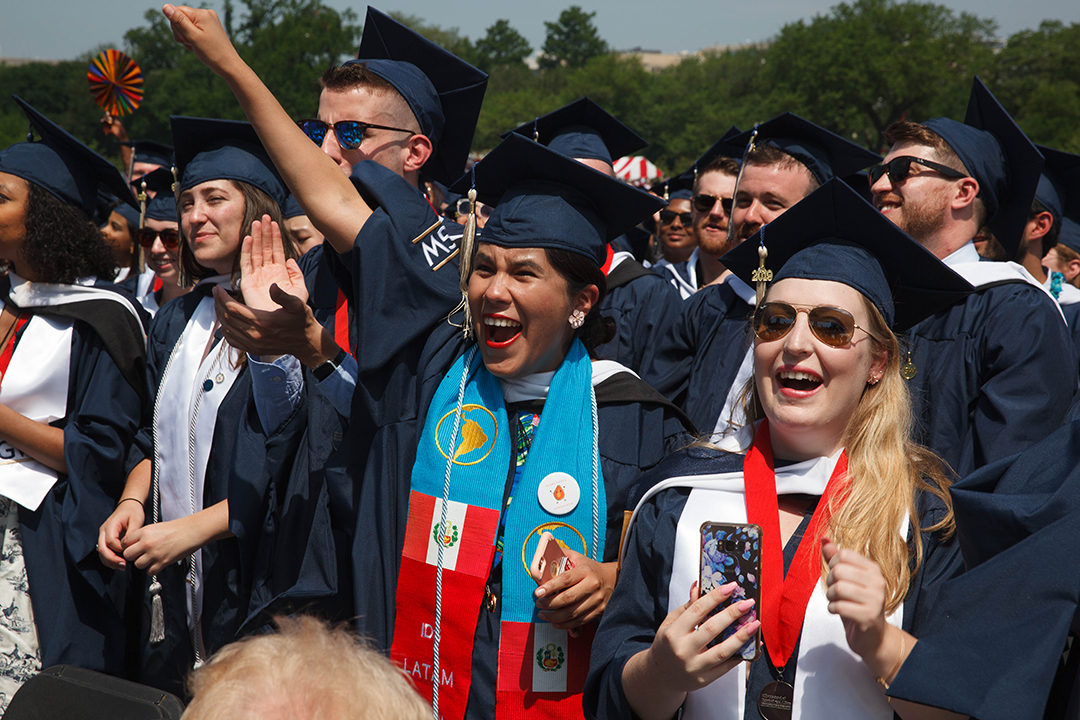 A group of 2019 graduates cheering. One is thrusting her fist into the air.