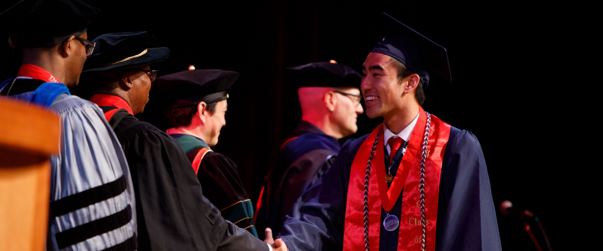 A male graduating student shaking hands with a dean