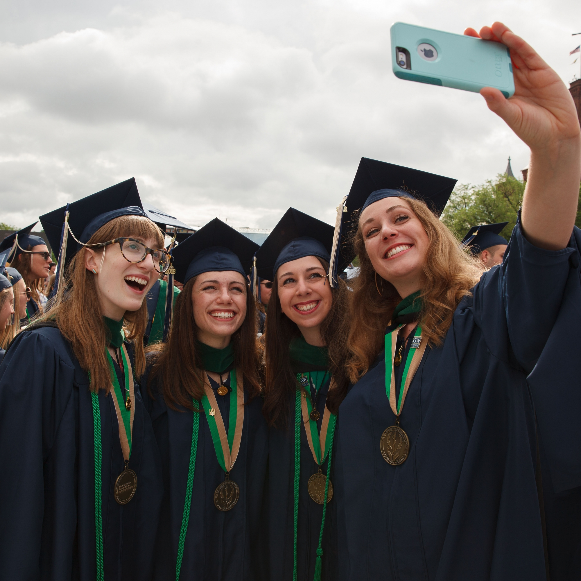A group of women in Commencement regalia taking a selfie and smiling