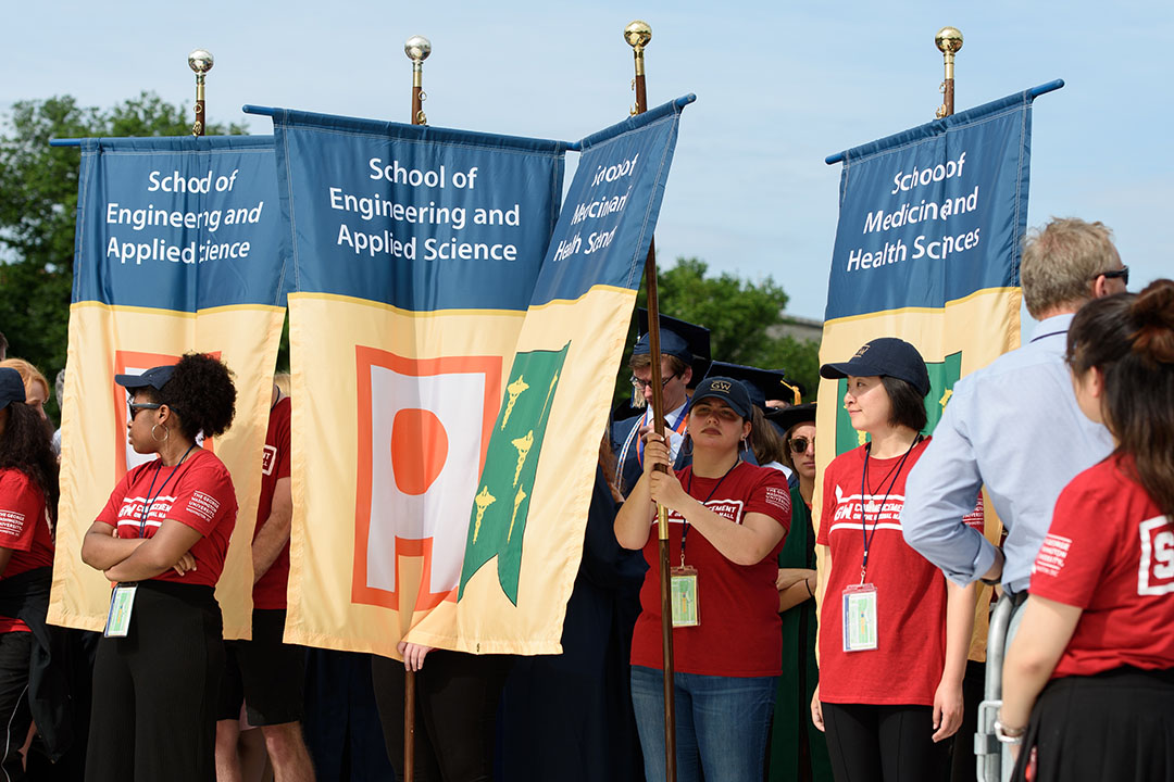 Student workers holding college banners at the commencement ceremony