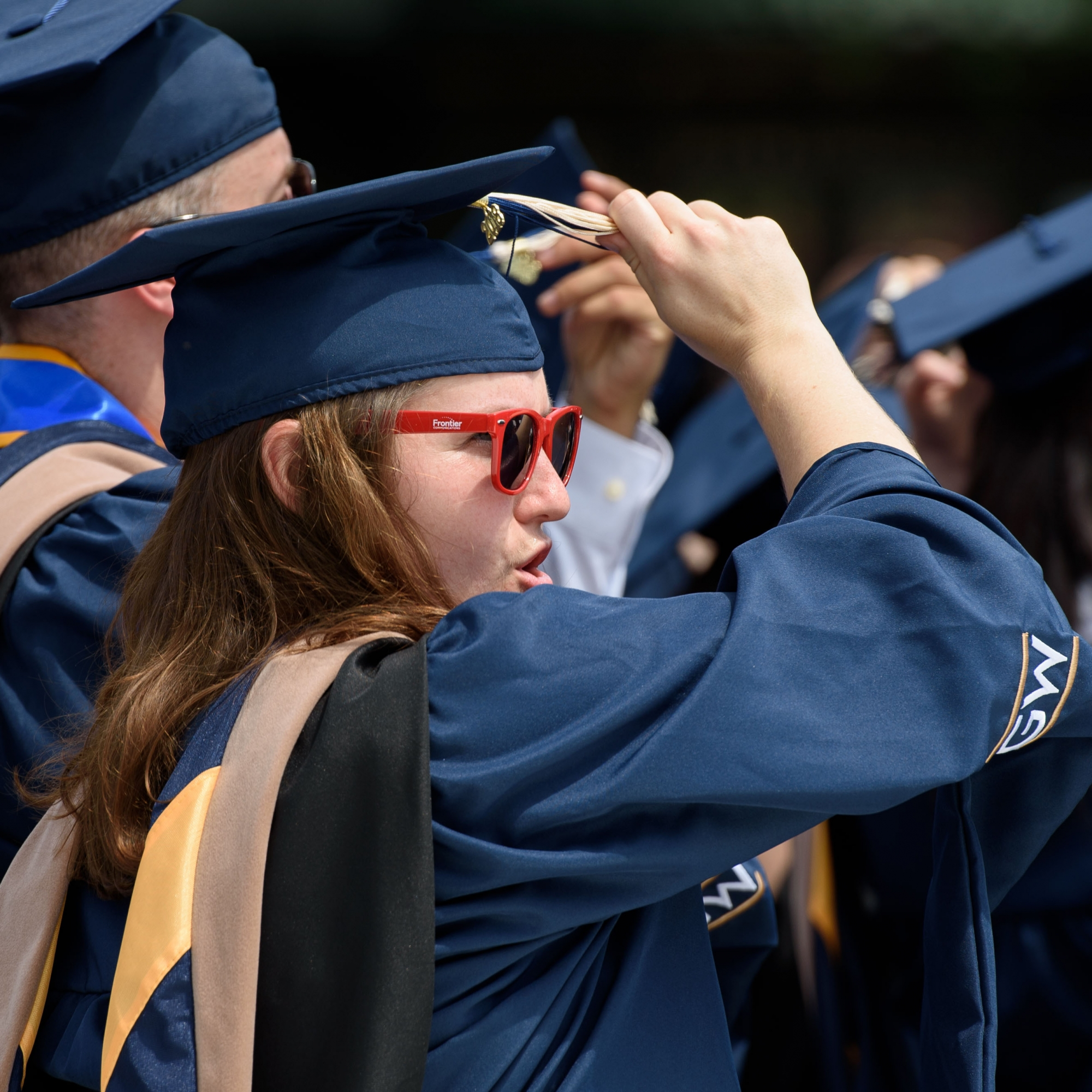 A female graduate moving her tassel and wearing sunglasses