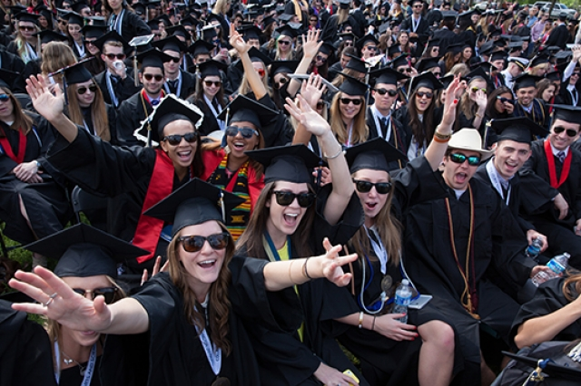 Graduates seated at the Commencement ceremony cheering and posing for the camera
