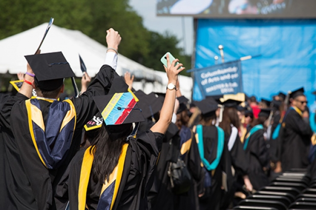 Graduates standing and cheering at Commencement