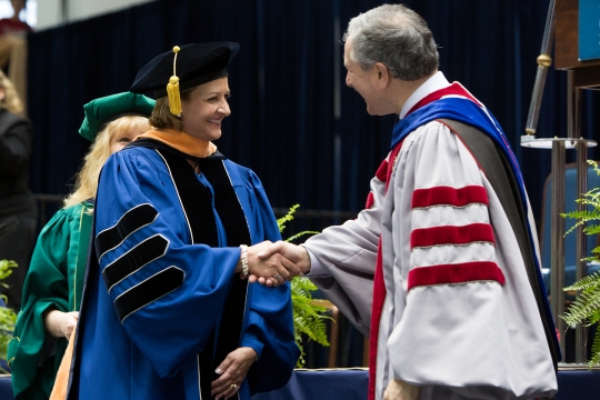 Doctoral candidate shaking Provost Lerman's hand after crossing the stage