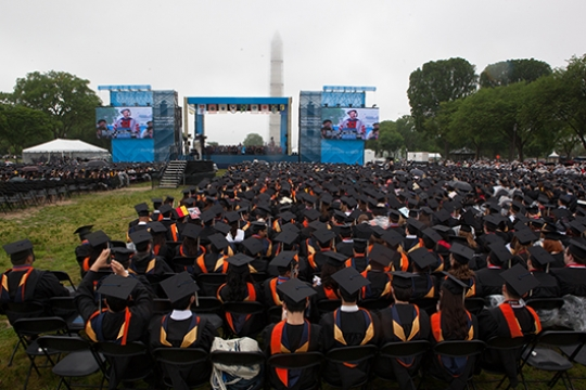 GW graduates looking at the stage with the Washington Monument in the background at University Commencement.