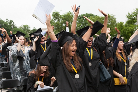 Students cheering with their arms in the air at commencement on the National Mall
